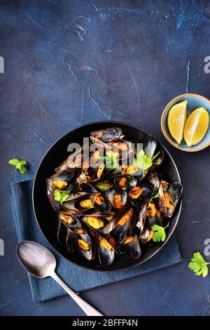 Vertikale Aufnahme von gekochten Muscheln auf blauem Hintergrund - Stockfoto