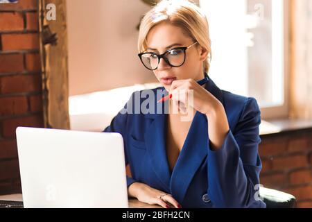 Closeup Portrait von jungen hübschen Blondine Business woman in Brille stilvolle blaue Jacke, weißer Laptop im Cafe, der die Feder, Ernst - Stockfoto