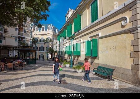 Menschen, die auf einer engen Kopfsteinpflasterstraße im historischen Viertel von Macau, China, spazieren gehen.