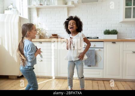 Glückliche kleine multiethnische Mädchen singen in der Küche zusammen - Stockfoto