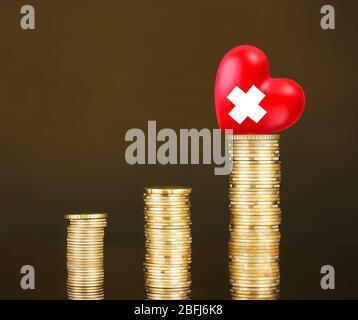 Rotes Herz mit Kreuz Zeichen auf Stapel von Münzen auf braunem Hintergrund - Stockfoto