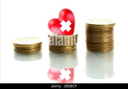 Rotes Herz mit Kreuz Zeichen auf Stapel von Münzen isoliert auf weiß - Stockfoto