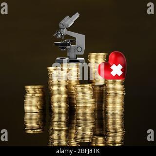 Rotes Herz mit Kreuzzeichen und Mikroskop auf einem Münzstapel auf dunkelbraunem Hintergrund - Stockfoto