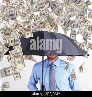 Geschäftsmann steht im Regen des Geldes - Stockfoto