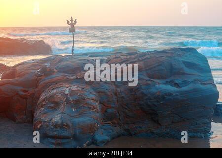 Shiva Face Rock Carving und Trident Totem am Vagator Beach, Goa, Indien. Schöner Sonnenuntergang Hintergrund. Nördlichster Strand von Bardez Taluka in Goa. Gegenposition