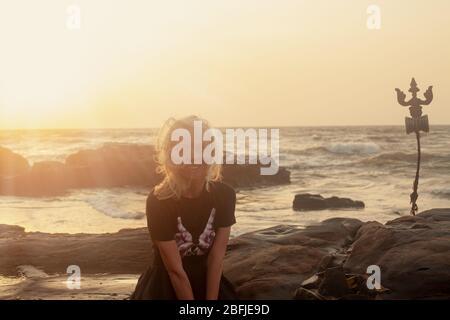 Trident totem in der Nähe schöne junge weiße Skined Frau sittind auf Shiva Gesicht Rock Carving auf Vagator Beach, Goa, Indien. Sonnenuntergang Hintergrund. Nördlichste - Stockfoto