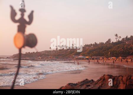 Trident totem in der Nähe von Shiva Face Rock Carving am Vagator Beach, Goa, Indien. Wunderschöner Sonnenuntergang und Uferhintergrund. Nördlichster Strand von Bardez Taluka in - Stockfoto