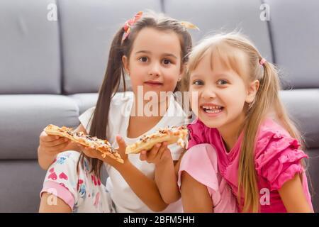 Zwei kleine Mädchen essen riesige Pizza zu Hause - Stockfoto