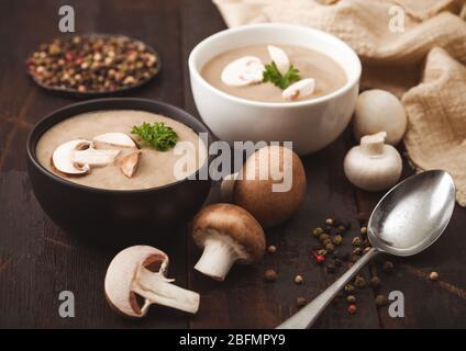 Keramische Schüssel Platten von cremig Kastanie champignon Pilzsuppe mit Löffel, Pfeffer und Küche Tuch auf dunklem Holz. - Stockfoto