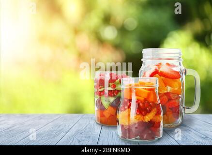 Gläser mit leckeren Salaten auf dem Tisch im Freien