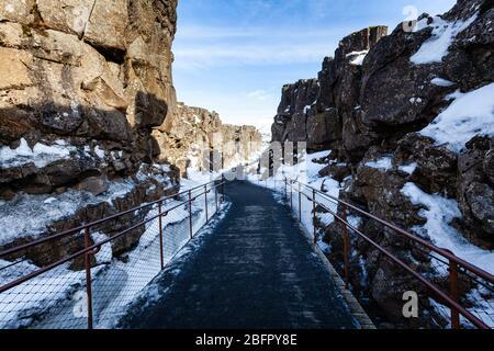 Pfad durch die Almannagja-Bruchlinie im Mittelatlantischen Rücken im Thingvellir (Þingvellir) Nationalpark im Südwesten Islands im Winter im Schnee - Stockfoto