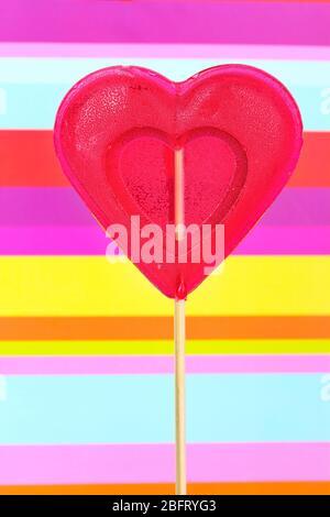 Roter Herz-Lollipop auf gestreiftem Hintergrund - Stockfoto