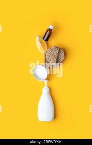 Kreatives Konzept umweltfreundlicher natürlicher Reinigungsmittel auf gelbem Küchentisch: Soda, ätherische Öle, Zellulose-Schwamm, Lumpen, Zitrone, Seife, Essig
