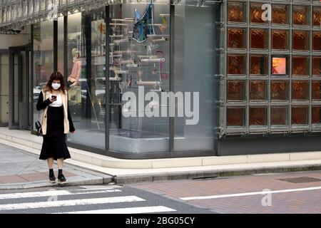 Eine Fußgänger-Maske in einer ungewöhnlich ruhigen Straße von Ginza Maison Hermes. Aufgrund des Coronavirus-Ausbruchs sind die Geschäfte im April 2020 geschlossen. - Stockfoto