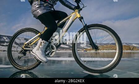 Frau fährt Fahrrad auf dem Eis. Reifen auf dem Fahrrad sind mit WI abgedeckt - Stockfoto