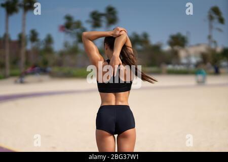 Morgendliches Workout. Gesundes Lifestyle-Konzept. Junge attraktive Frau in Sportbekleidung dehnt sich vor dem Sport am Strand bei Sonnenaufgang. Aufwärmen