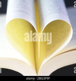 Quadratische herzförmige Buchseiten, selektiver Fokus auf einem schwarzen Hintergrund Konzept der Liebe zum Lesen