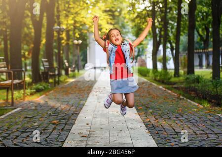 Kleines Mädchen gehen in die Schule mit Rucksack in den Morgen unter der warmen Sonne. Bildung Konzept. - Stockfoto
