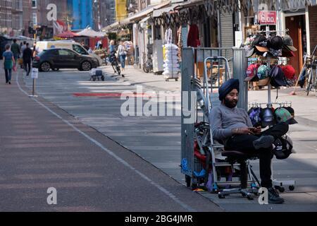 Corona-Krise: Ein einsamer Verkäufer auf dem berühmten Albert Cuyp-Markt in Amsterdam (Niederlande). Der Markt ist teilweise geschlossen. - Stockfoto