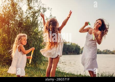 Muttertag. Mutter hilft Töchtern, Blasen im Frühlingspark zu blasen. Kinder, die Spaß beim Spielen und Bläschen fangen
