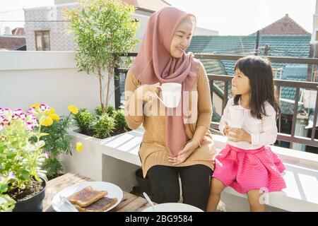 Mutter und Tochter muslim genießen ihr Frühstück im Garten