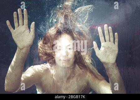 Frau unter Wasser. Eine junge Frau ist in einer Wasseroberfläche gefangen. Hände ruhen auf. Sommer-Gefühl. Unterwasser.