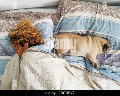Romantisches Beziehungskonzept Mensch und Hund - kaukasische Frau schläft zuhause mit ihrem lieblichen Pug auf dem Sofa - braune Farben und Haustiertherapie indo - Stockfoto