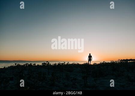 Silhouette eines Mannes, der den Sonnenuntergang am Strand genießt Stockfoto