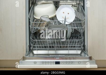 Fein gewaschene Speisen in der Spülmaschine. Integrierter Geschirrspüler mit weißen Platten Frontansicht und fröhliche Emotion auf Platte. Einfaches Hausreinigungskonzept. - Stockfoto