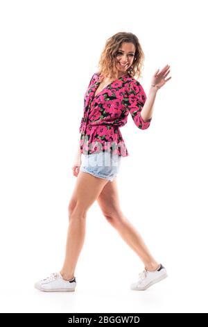 Seitenansicht der fröhlichen jungen stilvollen Frau, die weg geht und sich zurückdreht und Hand zum Abschied winkt. Ganzkörper isoliert auf weißem Hintergrund. - Stockfoto