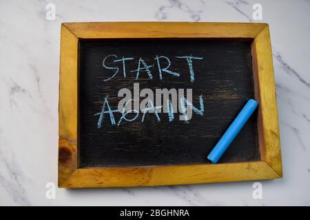 Beginnen Sie erneut auf eine Tafel auf Holztisch isoliert schreiben. - Stockfoto