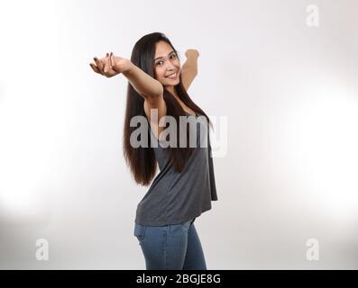 Eine junge attraktive Latina streckt ihre Arme weit aus, während sie lächelt. - Stockfoto