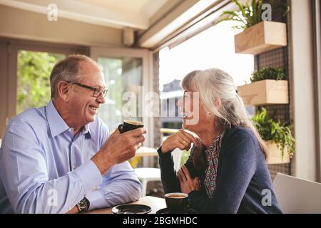 Fröhliches älteres Paar, das sich bei einer Tasse Kaffee im Café unterhielt. Pensionierte Mann und Frau sitzen im Café und unterhalten sich beim Kaffee. - Stockfoto