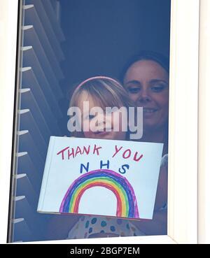 Brighton UK 22. April 2020 - EIN junges Mädchen und ihre Mutter kleben ein Dankeschön NHS Regenbogenmalerei und Nachricht an ihre Woodingdean Hausfenster in der Nähe von Brighton während der Sperrung in der Coronavirus COVID-19 Pandemie Krise . Quelle: Simon Dack / Alamy Live News
