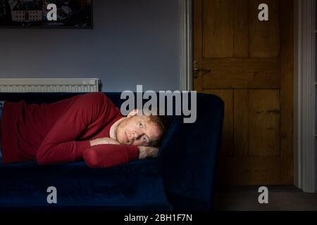 Mann im roten Sweatshirt auf Sofa liegend sieht traurig und Deprimiertes Denken und Nachdenken - Stockfoto