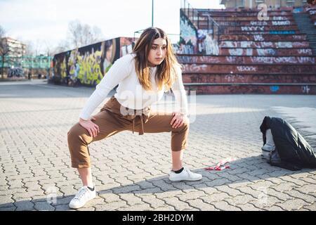 Junge Frau, die sich in einem Skatepark aufwärmt Stockfoto