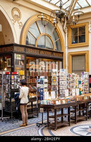 Junge Frau beim Einkaufen in einer Antiquitätenbuchhandlung in Passage Vivienne, Paris, Frankreich