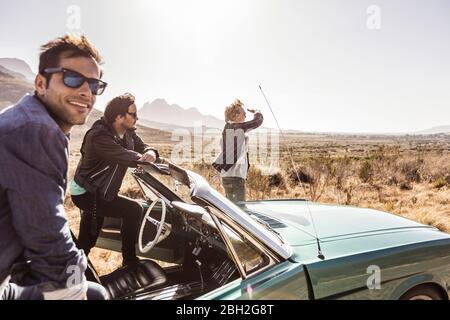 Glückliche Freunde auf einer Reise mit Cabrio