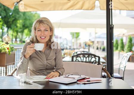 Porträt von reifen schöne blonde Frau seitlich schauen, kopieren Raum. Lächelnde Geschäftsfrau mittleren Alters, die Kaffee in einem Café im Freien trinkt - Stockfoto