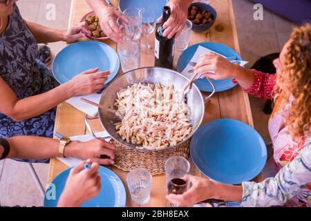 Genießen Sie das Abendessen mit Freunden. Blick von oben auf eine Gruppe von Leuten, die zusammen am rustikalen Holztisch zu Abend essen. Wein und italienische Pasta für ein schönes Nachtleben oder Mittagessen. Erwachsene und junge - Stockfoto