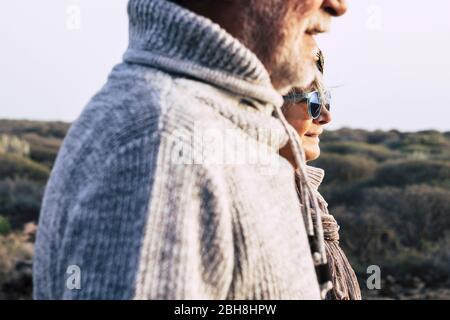 Portrait Fashion Style reifes Paar im Alter Senioren Mann und Frau mit der Natur im Hintergrund - kalte Jahreszeit Herbst oder Frühling und Sonne