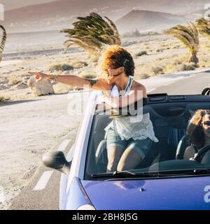 Glücklich blonde lockige Mädchen Reisenden auf einem Cabrio stehen und suchen die Schönheit des Ortes herum - Lifestyle und Reise-Urlaub Konzept die Welt genießen - paar Frauen fahren - Stockfoto