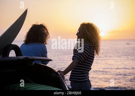 Ein paar Schönheitsfrauen im Urlaub genießen die Freundschaft vor einem colured Sonnenuntergang mit Ozean Horizont - Reise-und Lifestyle-Konzept für junge Menschen - lockiges Haar und Freiheit Bild - Stockfoto