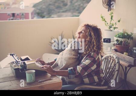 Schöne Mittelalter kaukasische Frau verwenden eine alte Vintage Schreibmaschine wie ein moderner Blogger auf Papier, während ihre schöne beste Freundin Mog Hund küssen sie mit Freundschaft Konzept - alternative Lifestyle Millennial - Stockfoto