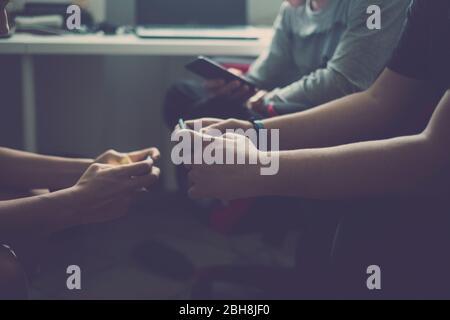 Nahaufnahme von drei Geräten mit Videospielen für junge kaukasische Freunde, die zu Hause wie Technologie-süchtig mit Handy und Internet-Anschluss spielen - Millennial Boy Concept