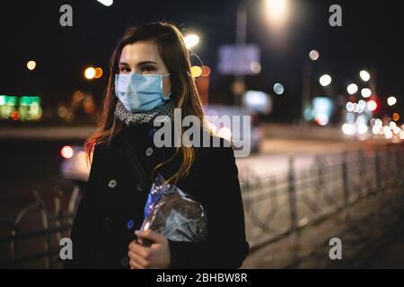 Porträt der jungen Frau mit Gesicht medizinische Maske mit Brot beim Spaziergang auf der Straße in der Stadt bei Nacht - Stockfoto