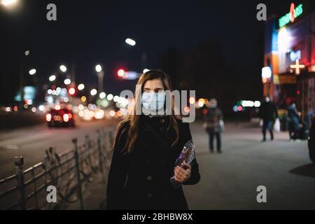 Porträt einer jungen Frau mit Gesicht medizinische Maske hält Brot, während auf der Straße der Stadt in der Nacht - Stockfoto
