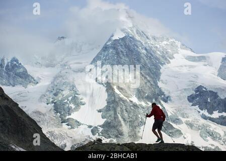 Männlicher Wanderer mit Wanderstöcken. Im Hintergrund ein erstaunlicher, felsiger Berg im Schnee in den Penniner Alpen. Bergwandern, Mann erreicht Gipfel. Wilde Natur mit herrlichem Ausblick. Sporttourismus in den Alpen.