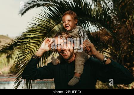 Lachender Vater, der seinem Sohn einen Huckepack-Ritt im Freien mit Sonnenlicht im Gesicht gibt.Lachen - Stockfoto