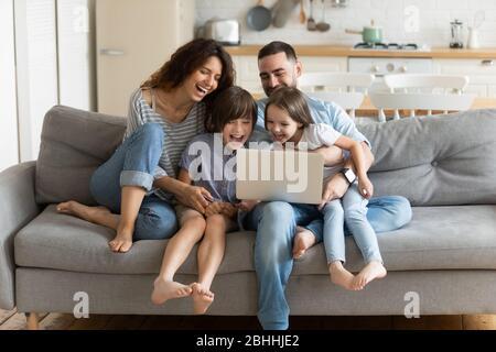 Überglücklich Kinder beim Betrachten von lustigen Videos auf dem Computer mit Eltern. - Stockfoto